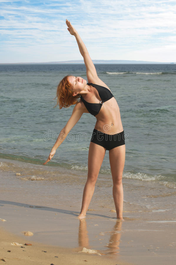Bella donna rossa che si esercita alla spiaggia fotografie stock
