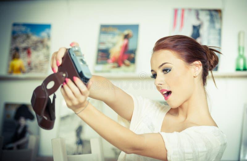 Bella, donna rossa sorridente dei capelli che prende le foto se stessa con una macchina fotografica Femmina attraente alla moda c fotografia stock