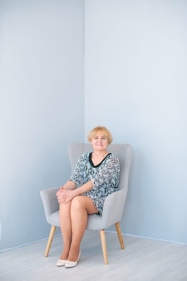 Bella donna senior che si siede sulla poltrona in studio blu-chiaro immagine stock libera da diritti