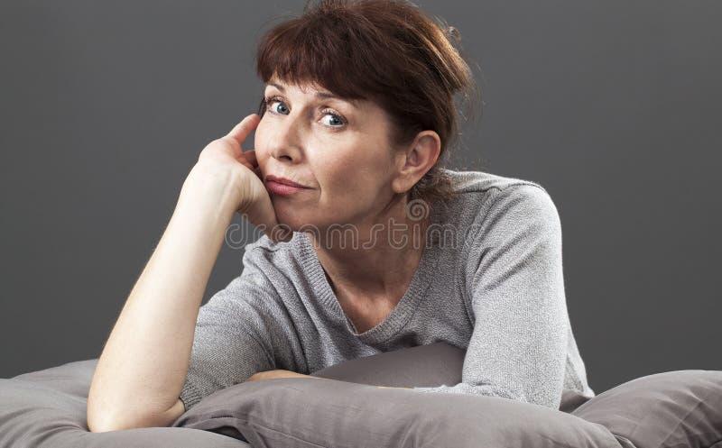 Bella donna senior sorridente che si riposa sui cuscini con soddisfazione fotografie stock libere da diritti