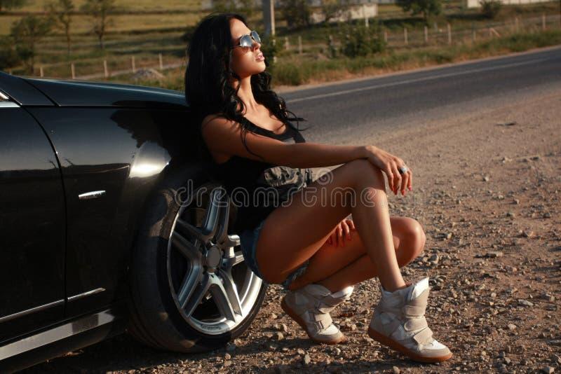Bella donna sexy che posa accanto ad un'automobile immagine stock libera da diritti