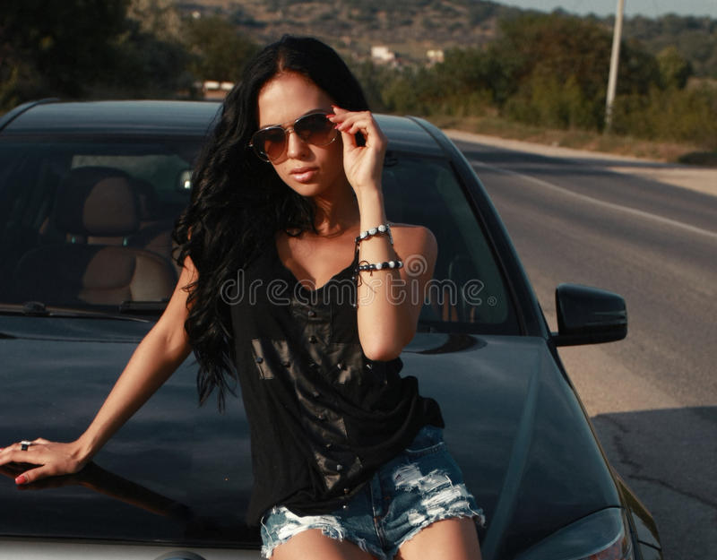 Bella donna sexy che posa accanto ad un'automobile fotografia stock libera da diritti