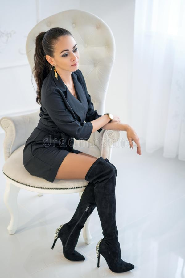Bella donna sicura alla moda che si siede in una sedia bianca nello studio immagini stock libere da diritti