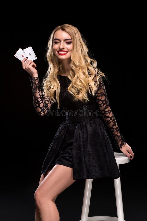 Bella donna sicura che si siede sulla sedia che mostra le carte che esaminano macchina fotografica con il posto della copia fotografia stock libera da diritti