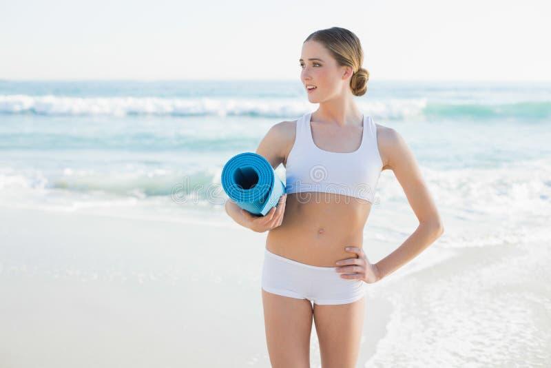 Bella donna snella che tiene la stuoia acciambellata di esercizio immagine stock