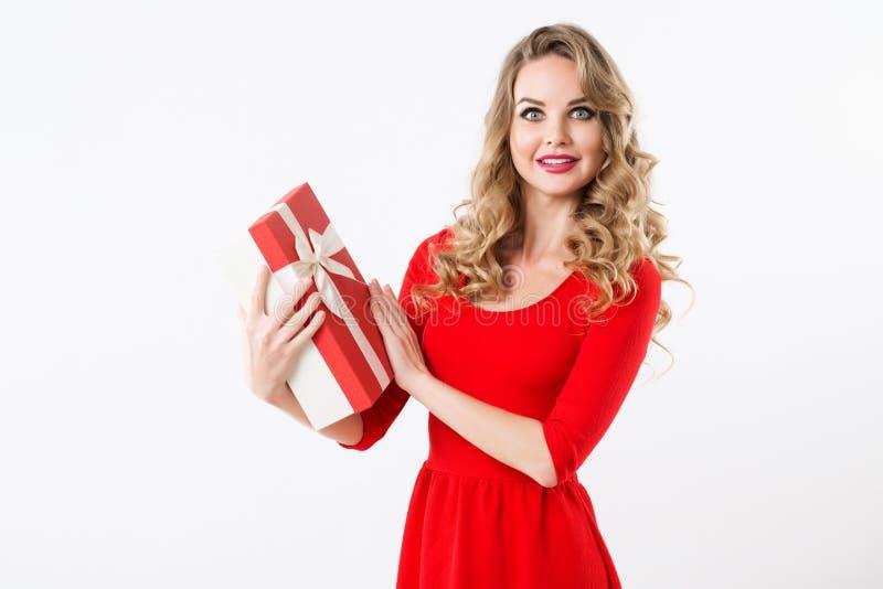 Bella donna sorpresa in un vestito rosso con un contenitore di regalo in sue mani fotografia stock