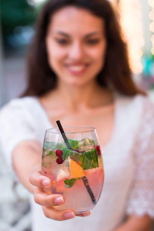 Bella donna sorridente che beve la bacca fredda della limonata, all'aperto fotografia stock