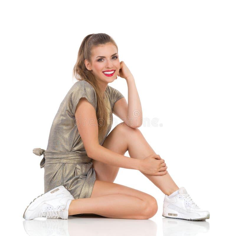 Bella donna sorridente che si siede su un pavimento immagini stock libere da diritti