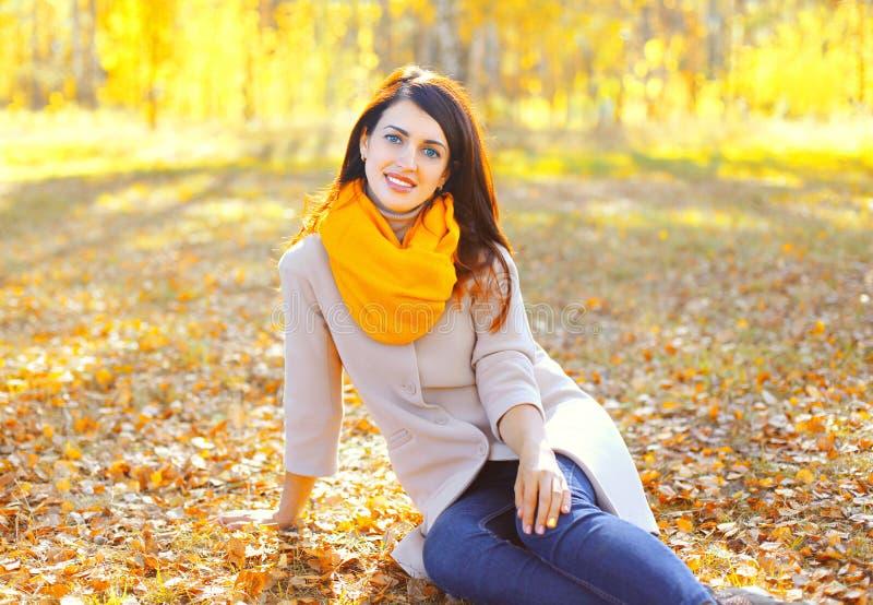 Bella donna sorridente che si siede sulle foglie in autunno soleggiato fotografia stock