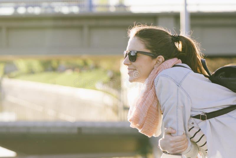 Bella donna sorridente con gli occhiali da sole, appoggiantesi il ponte fotografia stock
