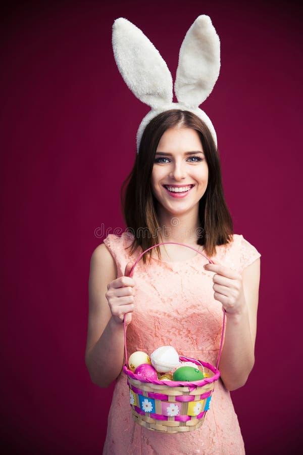Bella donna sorridente con un canestro dell'uovo di Pasqua fotografie stock libere da diritti
