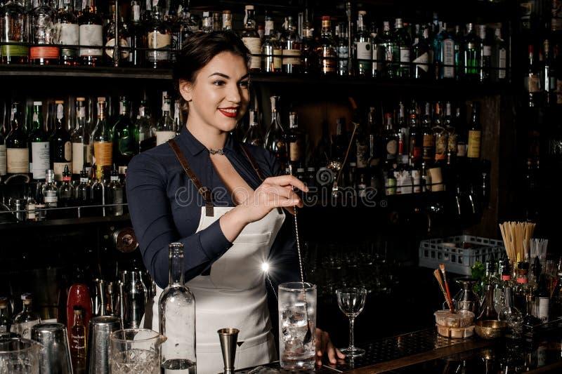 Bella donna sorridente del barista che mescola la bevanda fresca di estate fotografia stock libera da diritti