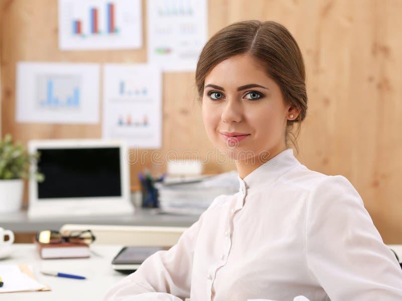 Bella donna sorridente di affari che si siede nel luogo di lavoro dell'ufficio fotografia stock