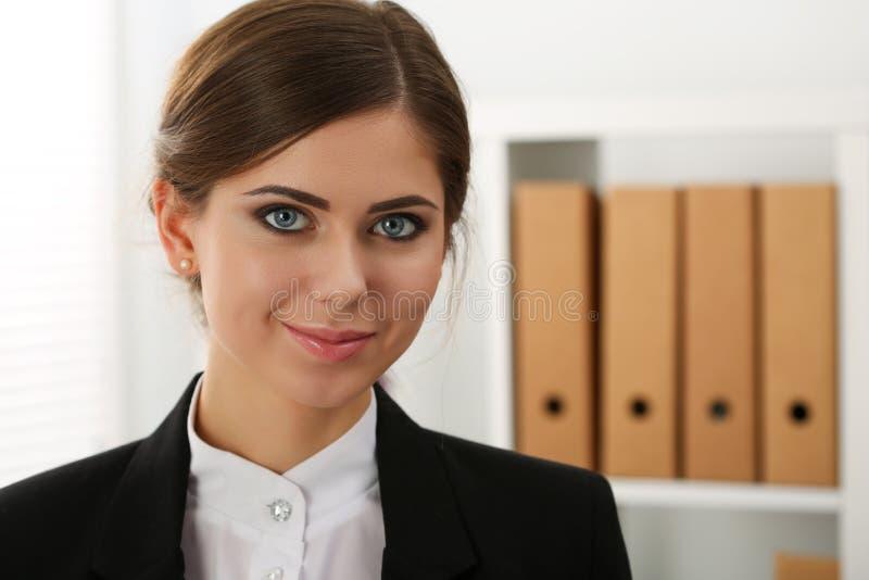 Bella donna sorridente di affari che sta all'ufficio fotografia stock libera da diritti