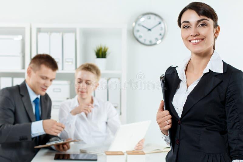 Bella donna sorridente di affari in lavagna per appunti della tenuta del vestito nell'ha immagini stock