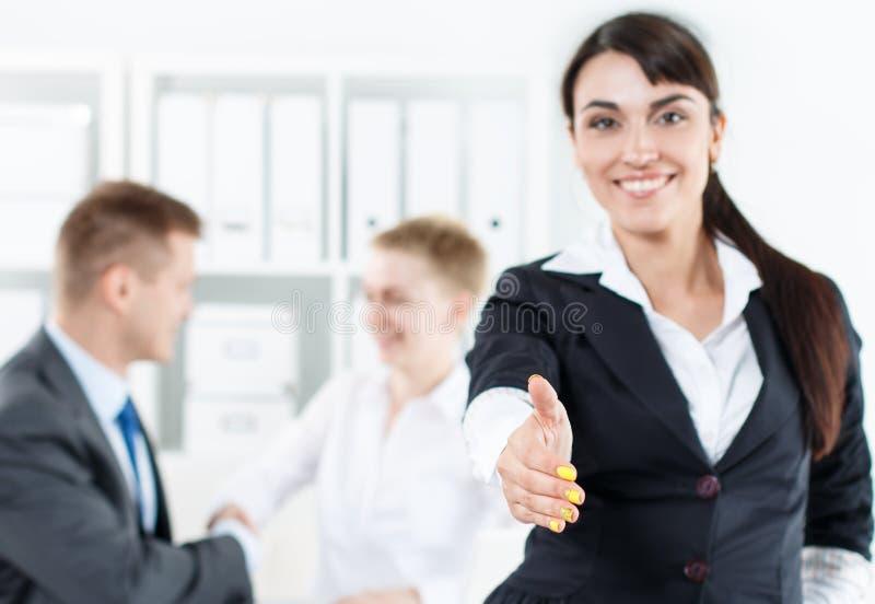 Bella donna sorridente di affari in mano d'offerta del vestito alla scossa immagine stock