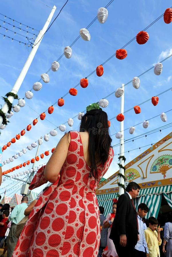 Bella donna spagnola che cammina giù una via dalla fiera, Sevilla, Andalusia, Spagna fotografia stock