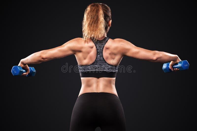 Bella donna sportiva ed adatta con la testa di legno che si esercita al fondo nero per restare adatto Motivazione di allenamento  fotografie stock