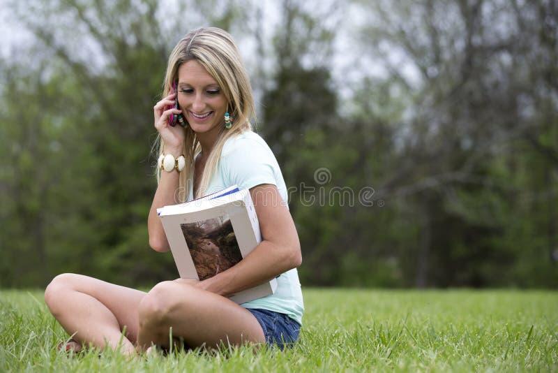 Bella donna sui libri della tenuta del cellulare fotografie stock