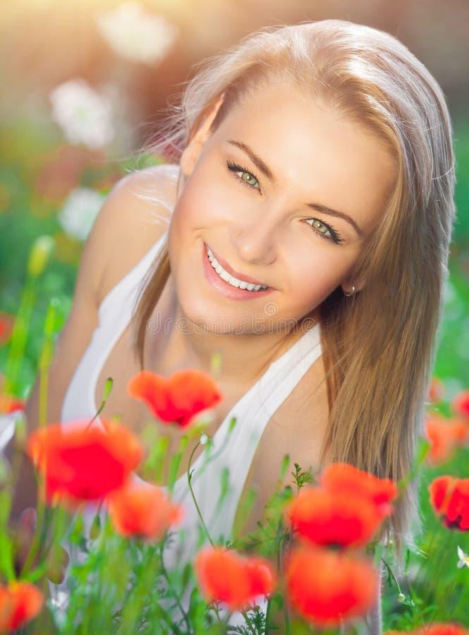 Bella donna sul campo del papavero fotografia stock