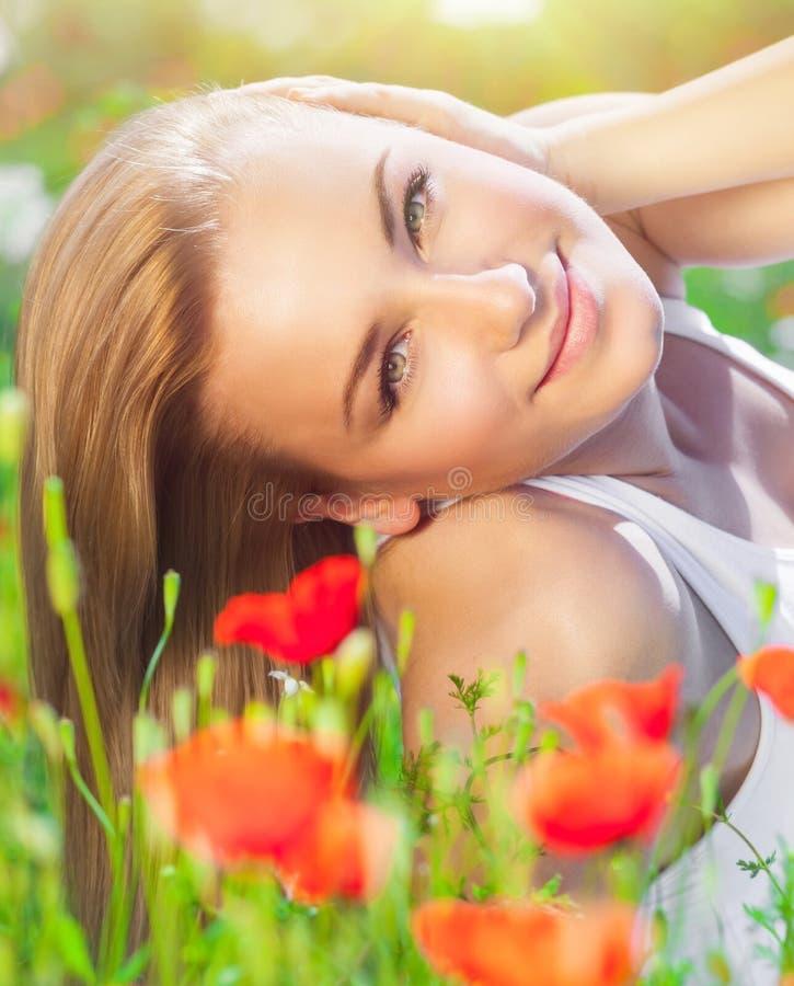 Bella donna sul giacimento di fiore del papavero fotografie stock