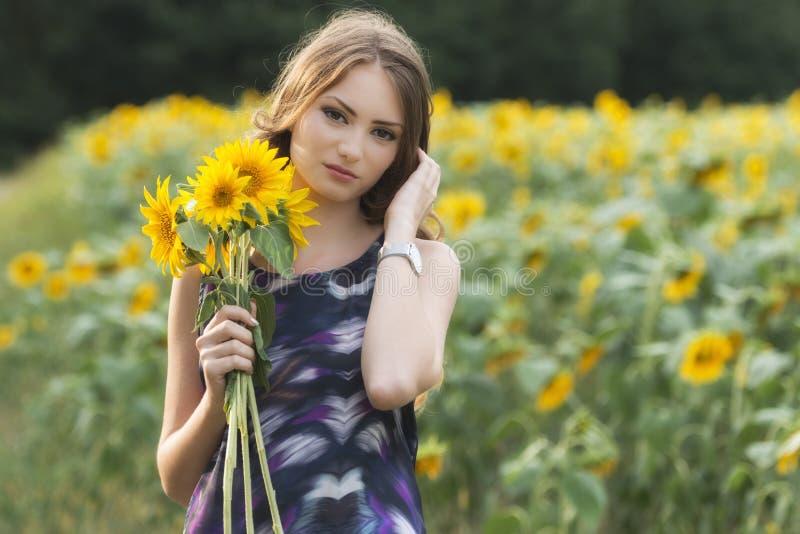 Bella donna sul giacimento di fioritura del girasole di estate immagini stock libere da diritti