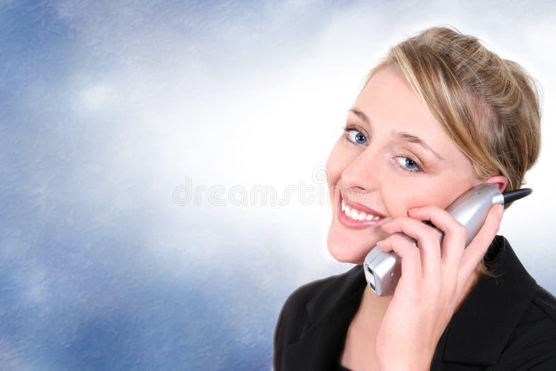 Bella Donna Sul Telefono Senza Cordone Della Camera Contro Priorità Bassa Blu Fotografie Stock Libere da Diritti