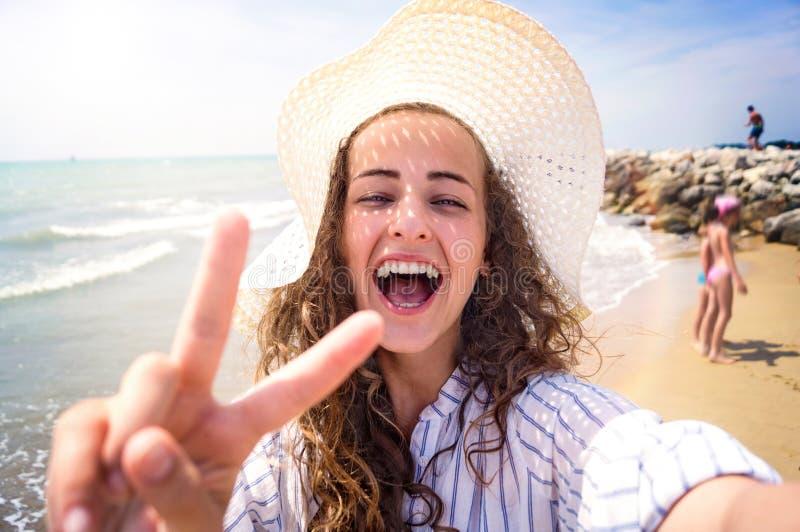 Bella donna sulla spiaggia, ridere, prendente selfie, giorno soleggiato fotografie stock