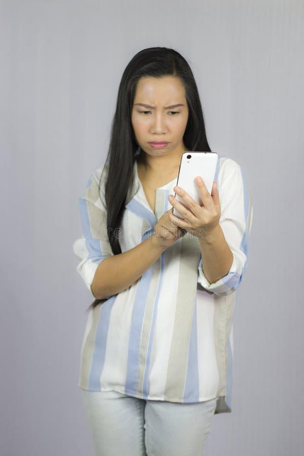 Bella donna sveglia in camicia che agisce giocante sul telefono Isolato su priorit? bassa grigia immagini stock libere da diritti