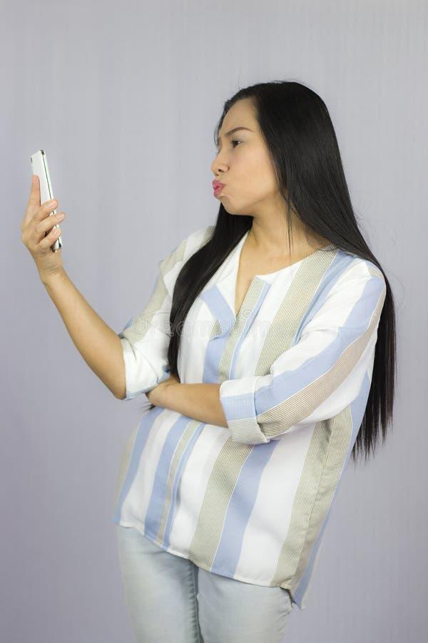 Bella donna sveglia in camicia che agisce giocante sul telefono Isolato su priorit? bassa grigia immagine stock