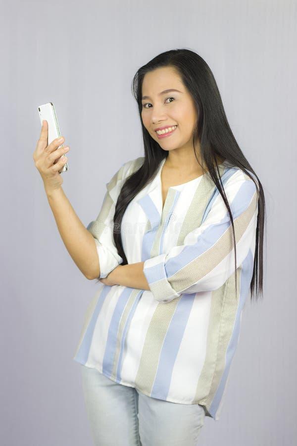 Bella donna sveglia in camicia che agisce giocante sul telefono Isolato su priorit? bassa grigia fotografia stock libera da diritti