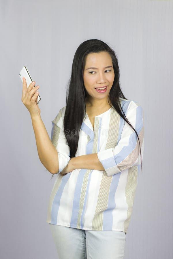 Bella donna sveglia in camicia che agisce giocante sul telefono Isolato su priorit? bassa grigia fotografia stock