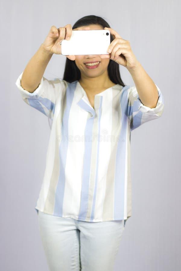 Bella donna sveglia in camicia che agisce giocante sul telefono Isolato su priorit? bassa grigia immagine stock libera da diritti