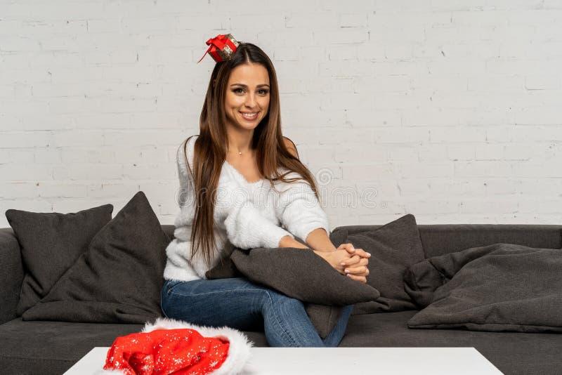Bella donna sveglia in cappello di Santa che si siede sul sofà e che posa con il fronte sorridente fotografia stock libera da diritti