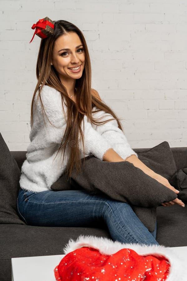 Bella donna sveglia in cappello di Santa che si siede sul sofà e che posa con il fronte sorridente fotografie stock libere da diritti