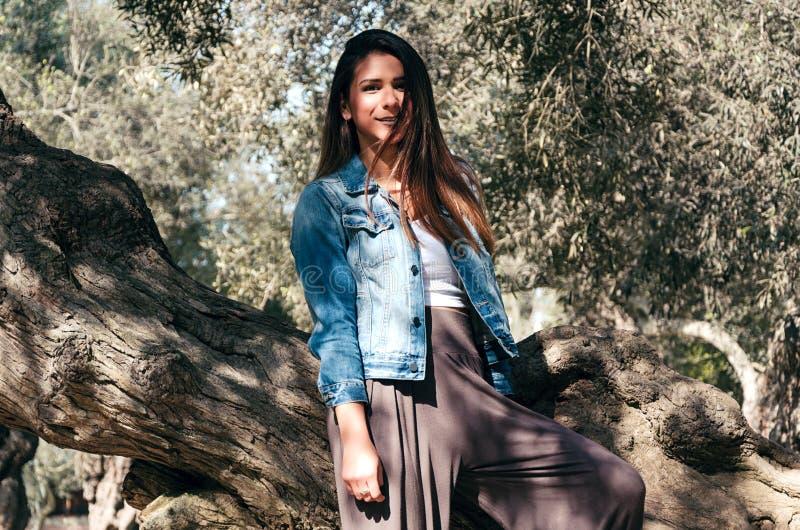 Bella donna teenager dai capelli lunghi con capelli marroni che si appoggiano un albero fotografia stock