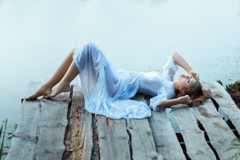 Bella donna tenera che si trova sul molo e annoiata immagini stock libere da diritti