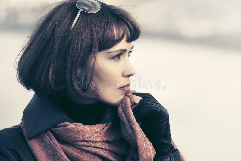 Bella donna triste di modo in cappotto di cuoio all'aperto fotografia stock