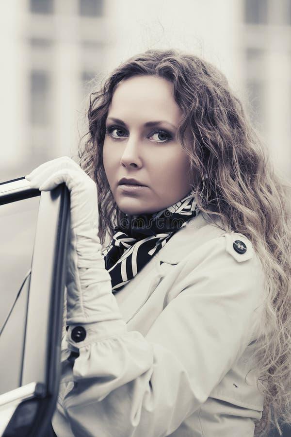 Bella donna triste di modo in trench bianco fuori della sua automobile fotografia stock