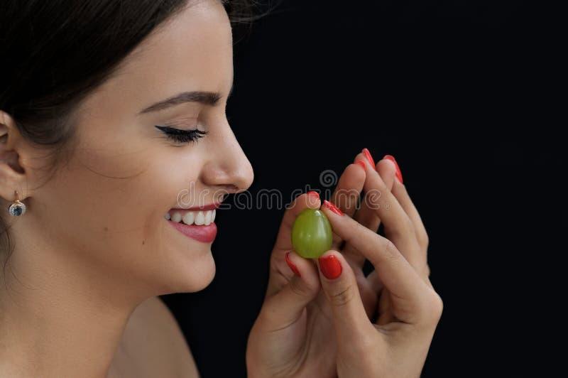 Bella donna turca che tiene un'uva in sue mani fotografie stock