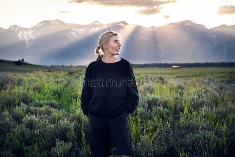 Bella donna turistica che viaggia e godere del Mountain View della natura nel campo verde su una vacanza di estate nella nazione  immagini stock