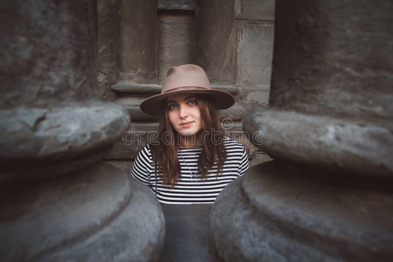 Bella donna in un cappello ed in una camicia a strisce che esaminano la macchina fotografica Ritratto del primo piano immagine stock