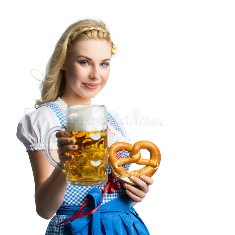Bella donna in un dirndl bavarese tradizionale con birra e la ciambellina salata fotografia stock