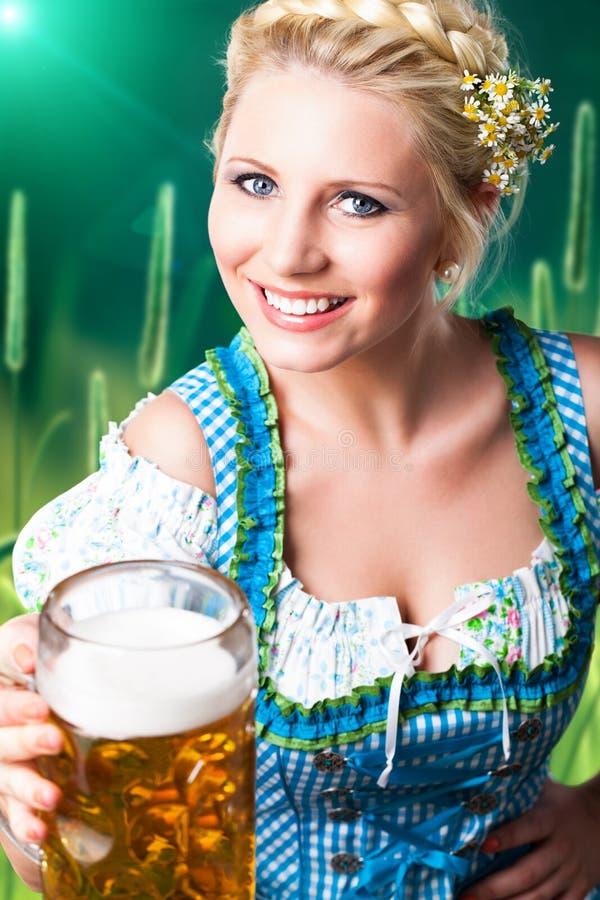 Bella donna in un dirndl bavarese tradizionale con una birra immagini stock