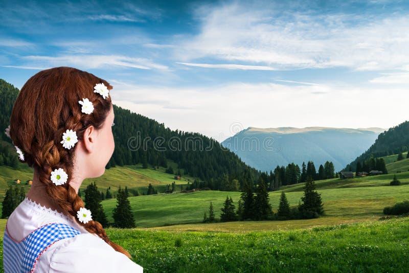Bella donna in un dirndl bavarese tradizionale davanti ad un paesaggio della montagna immagini stock