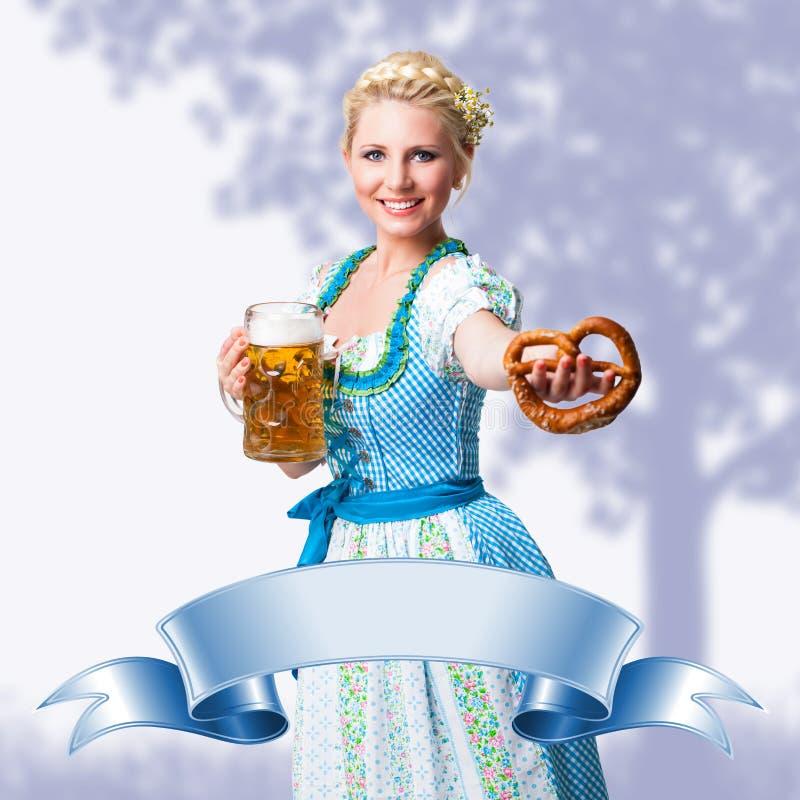 Bella donna in un dirndl bavarese tradizionale davanti ad una scena della molla e ad un nastro vuoto fotografie stock libere da diritti