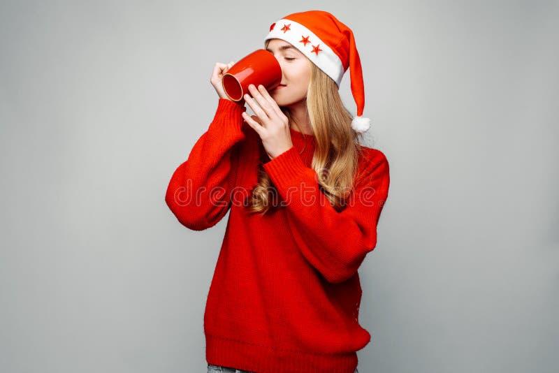 Bella donna in un maglione rosso, portante un cappello di Santa Claus, con una tazza rossa, caffè bevente, su un fondo grigio immagini stock libere da diritti