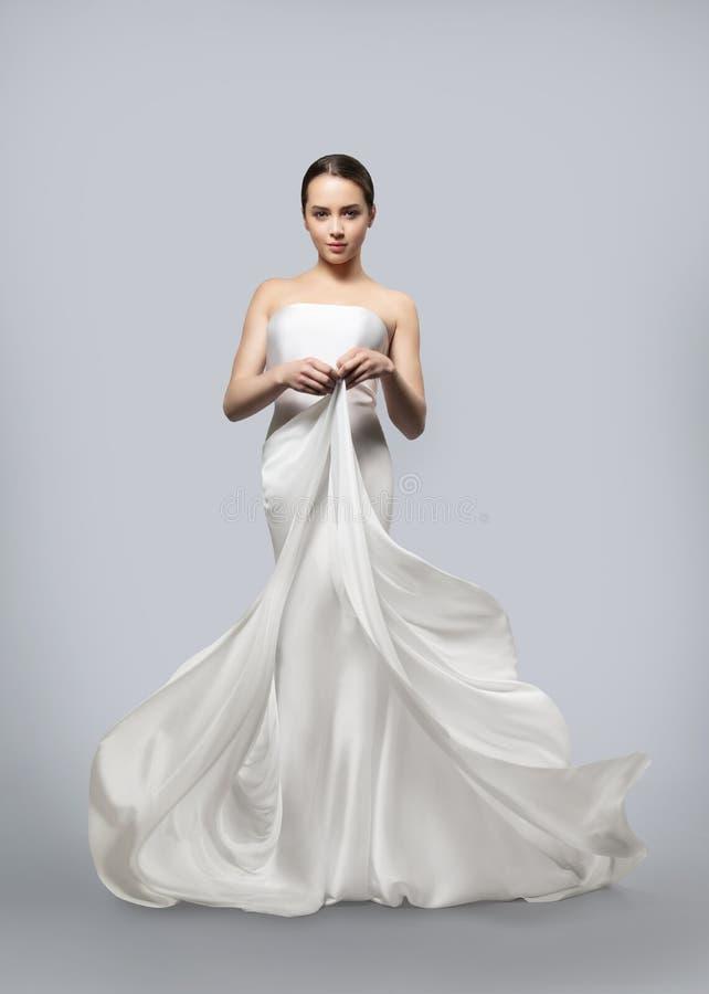 Bella donna in un vestito bianco d'ondeggiamento leggero Il tessuto leggero vola nel vento Priorit? bassa grigio-chiaro fotografia stock