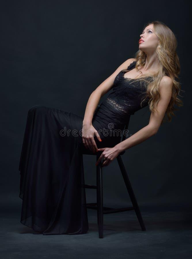 Bella donna in un vestito da sera nero che posa con la sedia fotografie stock