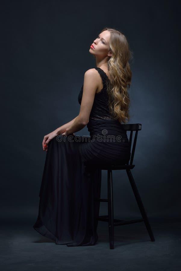 Bella donna in un vestito da sera nero che posa con la sedia immagini stock libere da diritti